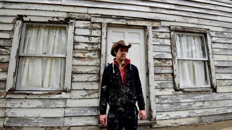 Artist Ryan Mendoza poses in front of Rosa Parks' house during which he helped rescue from Detroit and rebuilt it in his garden