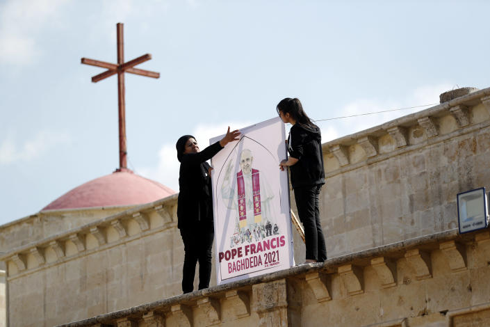Iraqi Christians place a poster at Church of the Immaculate Conception in Qaraqosh, Iraq Tuesday, Feb. 23, 2021. Pope Francis will visit the church during his historic trip to Iraq. Damaged during the Islamic State reign of terror, the church's tragedy mirrored that of its Christian community which was devastated by the group. (AP Photo/Hadi Mizban)
