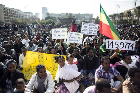 African migrants hold signs during a protest in Tel Aviv