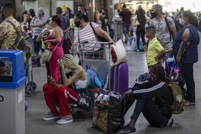 Travelers wait to board an inter-state bus, amid the COVID-19 pandemic in Sao Paulo, Brazil, Wednesday, Dec. 30, 2020. Despite rising infection numbers in the country, Brazilians are flocking to airports and taking to the highways to visit friends and loved ones to usher in the new year and take advantage of a long weekend. (AP Photo/Andre Penner)