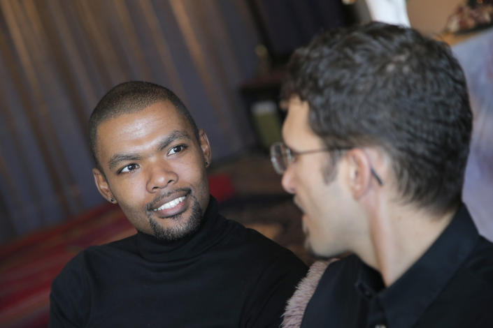 "In this photo taken on Monday, Oct. 22, 2012, Ludovic-Mohamed Zahed, right, who married his live-in partner Qiyaammudeen Jantjies, left, in South Africa, where gay marriage is recognized, during an interview with the Associated Press in Sevran, outside Paris. A plan to legalize same-sex marriage and allow gay couples to adopt was a liberal cornerstone of French President Francois Hollande's election manifesto earlier this year. It looked like a shoo-in, supported by a majority of the French, and an easy way to break with his conservative predecessor. But that was then, Now, as the Socialist government prepares to unveil its draft ""marriage for everyone"" law Wednesday, polls show wavering support for the idea and for the president amid increasingly vocal opposition in this traditionally Catholic country. Ludovic-Mohamed Zahed, who married his live-in partner Qiyaammudeen Jantjies in South Africa, where gay marriage is recognized, is already seeking instruction from his local town council to get his marriage recognized in France as soon as he can. (AP Photo/Christophe Ena)"