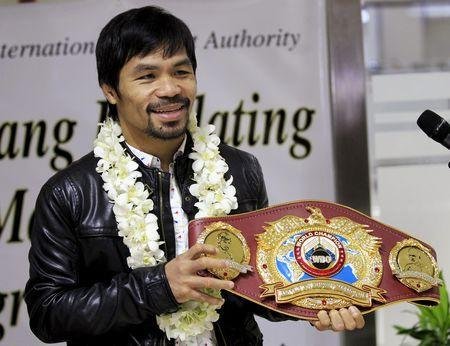 FILE PHOTO: Filipino boxing champion Manny Pacquiao shows his WBO championship belt to the media after defeating Timothy Bradley, upon his arrival at the Ninoy Aquino International Airport in Manila April 14, 2016. REUTERS/Romeo Ranoco Picture Supplied by Action Images