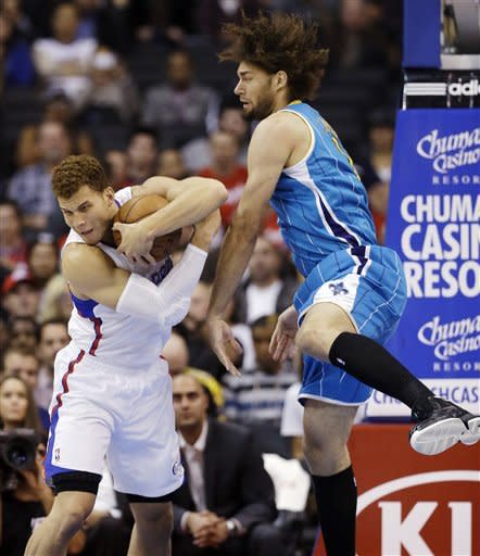Los Angeles Clippers power forward Blake Griffin, left, pulls a rebound away from New Orleans Hornets center Robin Lopez during the first half of an NBA basketball game in Los Angeles, Monday, Nov. 26, 2012. (AP Photo/Chris Carlson)
