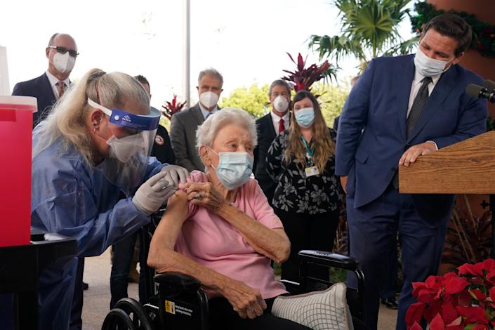 Florida Governor Ron DeSantis watches nurse Christine Philips deliver the Pfizer BioNTech vaccine for COVID-19 to Vera Leip, 88, who first lives in John Knox Village on December 16 in Pompano Beach, Florida State to get the vaccine.