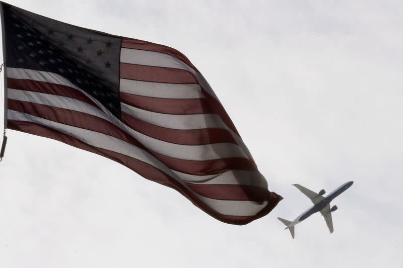 A Delta Airlines flight takes off past a U.S. flag in Boston