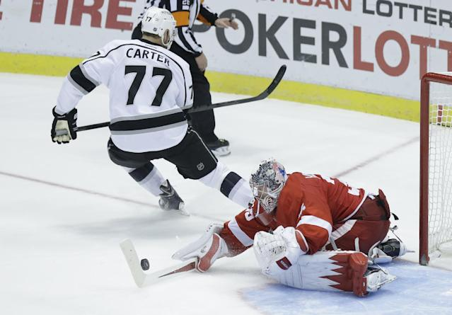 Detroit Red Wings goalie Jimmy Howard (35) stops a shot by Los Angeles Kings center Jeff Carter (77) during the shootout period of an NHL hockey game in Detroit, Saturday, Jan. 18, 2014. Detroit defeated Los Angeles 3-2. (AP Photo/Carlos Osorio)