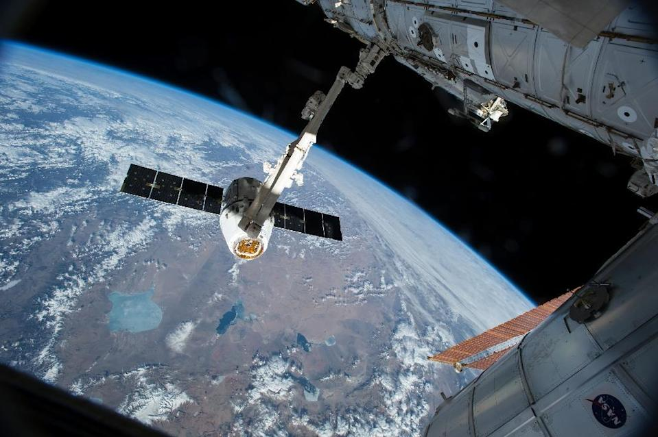 This NASA image taken April 17, 2015 shows the Canadarm 2 reaching out to grapple the SpaceX Dragon cargo spacecraft and prepare it to be pulled into its port on the International Space Station (AFP Photo/)