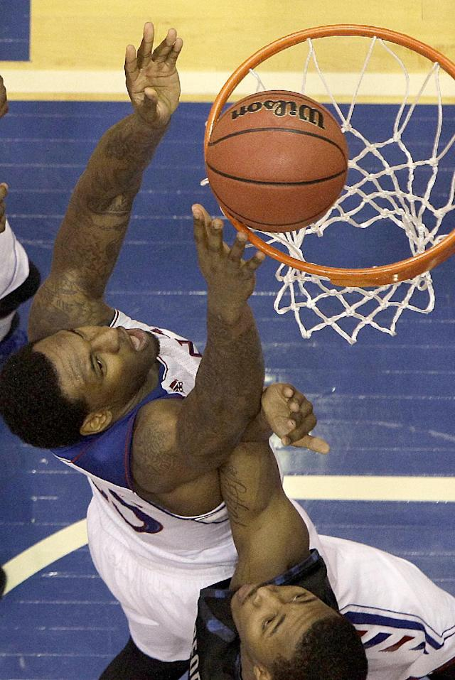 Kansas' Tarik Black, top, gets past Georgetown's Mikael Hopkins to put up a shot during the first half of an NCAA college basketball game Saturday, Dec. 21, 2013, in Lawrence, Kan. Kansas won the game 86-64. (AP Photo/Charlie Riedel)