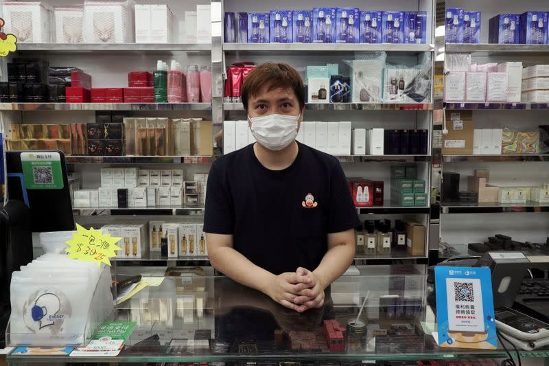 Cosmetics store owner David So poses for photo in Hong Kong's northern town of Sheung Shui