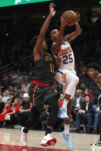 Phoenix Suns forward Mikal Bridges (25) goes to the basket as Atlanta Hawks forward De'Andre Hunter (12) defends in the first half of an NBA basketball game Tuesday, Jan. 14, 2020, in Atlanta. (AP Photo/John Bazemore)