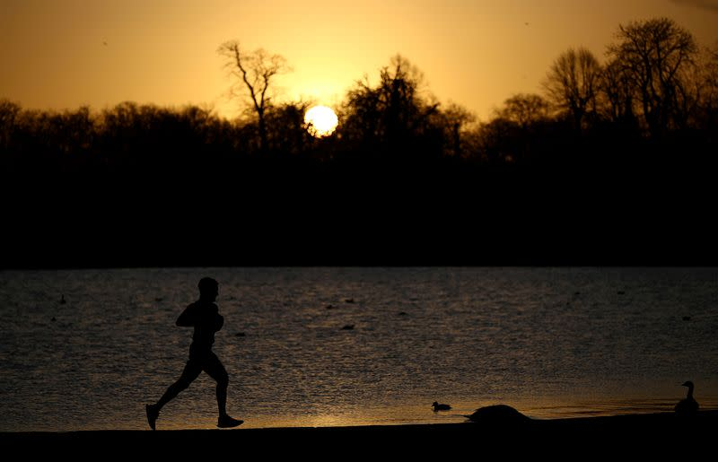 FILE PHOTO: A man jogs past the Round Pond in Kensington Palace Gardens as the sun rises in London