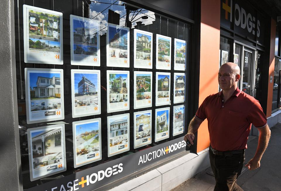 A man walks past a real estate agent's window advertising houses for sale and auction in Melbourne on May 1, 2019. - Australian property prices fell faster in the past year than at any time since the global financial crisis, a closely watched report said May 1, fuelling speculation of a pre-election interest rate cut. (Photo by William WEST / AFP)        (Photo credit should read WILLIAM WEST/AFP via Getty Images)