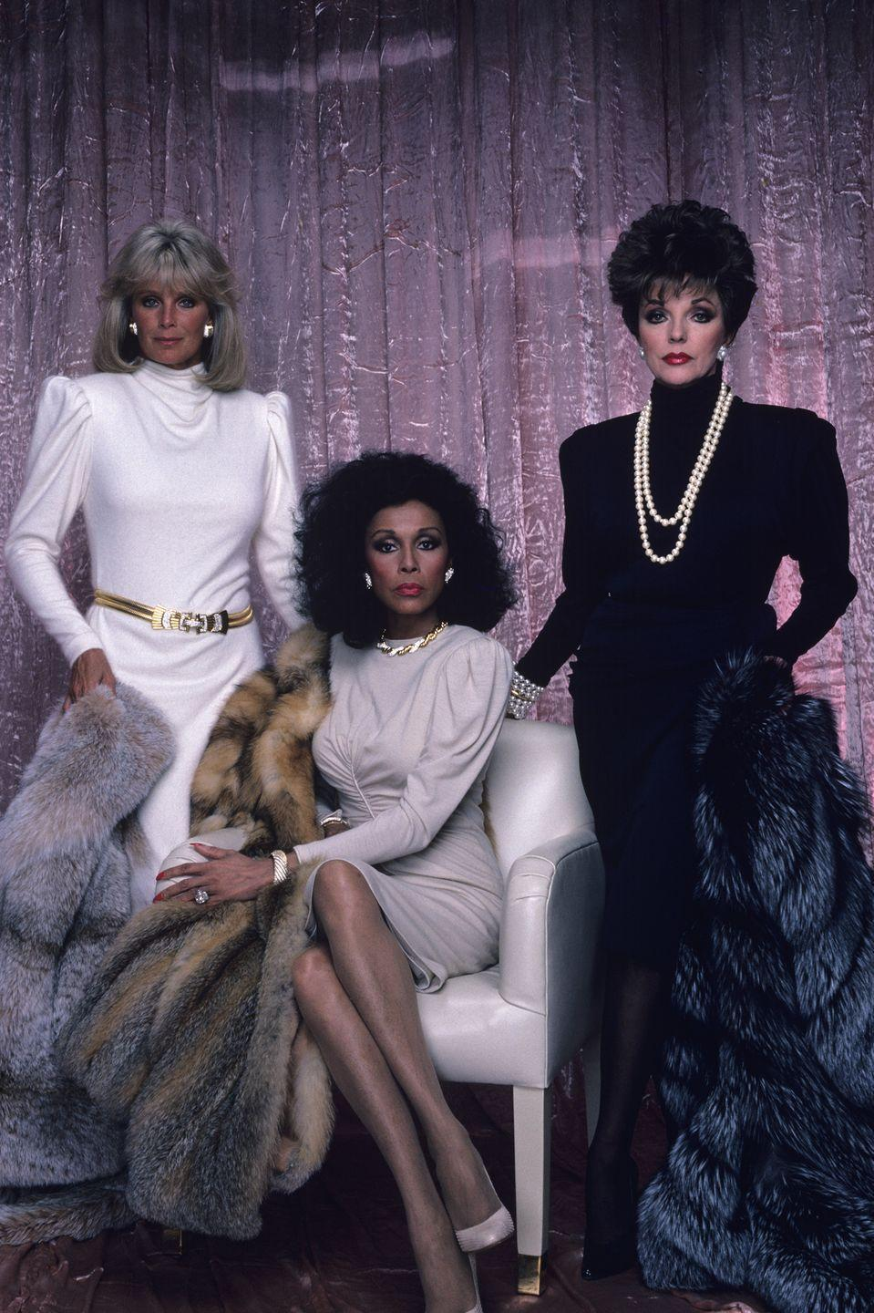 <p>Linda Evans, Diahann Carroll, and Joan Collins wearing shoulder pad dresses, pearls, and fur coats in a <em>Dynasty </em>promo photo.</p>
