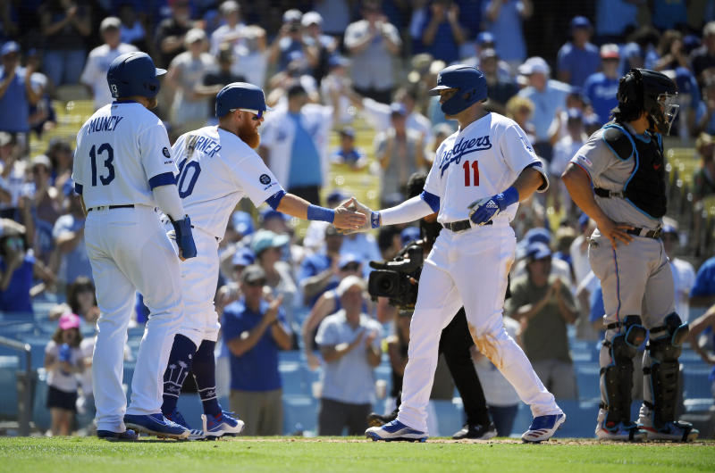 Los Angeles Dodgers' A.J. Pollock, second from right, is congratulated by Max Muncy, left, and Justin Turner, second from left, after hitting a three-run home run as Miami Marlins catcher Jorge Alfaro, right, stands at the plate during the seventh inning of a baseball game Sunday, July 21, 2019, in Los Angeles. (AP Photo/Mark J. Terrill)