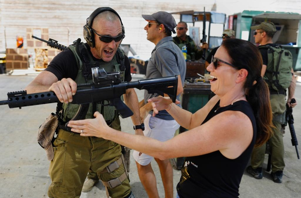 "Foreign tourists are taught how to use a gun during an ""anti-terrorism"" course in the West Bank on July 18, 2017 (AFP Photo/MENAHEM KAHANA)"