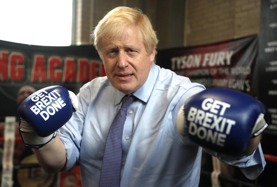 """MANCHESTER, ENGLAND - NOVEMBER 19: Britain's Prime Minister Boris Johnson poses for a photo wearing boxing gloves emblazoned with """"Get Brexit Done"""" during a stop in his General Election Campaign trail at Jimmy Egan's Boxing Academy on November 19, 2019 in Manchester, England. Britain goes to the polls on Dec.12. (Photo by Frank Augstein - WPA Pool/Getty Images)"""