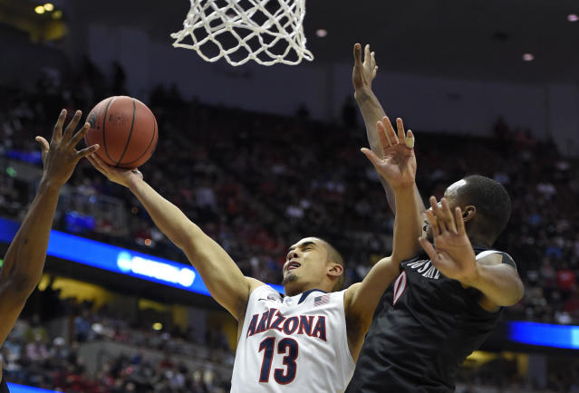 Arizona guard Nick Johnson (13) drives past San Diego State forward Skylar Spencer (0) during the first half in a regional semifinal NCAA college basketball tournament game, Thursday, March 27, 2014, in Anaheim, Calif. (AP Photo/Mark J. Terrill)