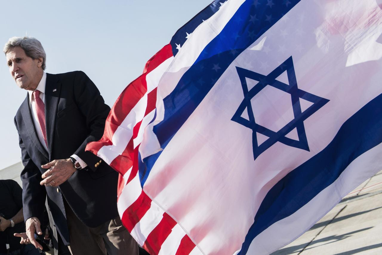 U.S. Secretary of State John Kerry walks past American (back) and Israeli flags at Ben Gurion International Airport in Tel Aviv January 6, 2014. REUTERS/Brendan Smialowski/Pool (ISRAEL - Tags: POLITICS)