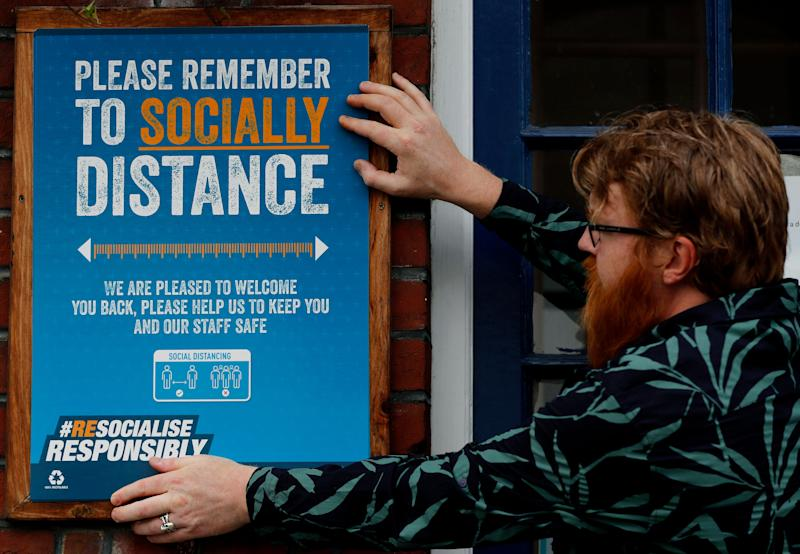 Are Kjetil Kolltveit puts up social distancing signs at the Chandos Arms pub in London ahead of 'Super Saturday' (Photo: ASSOCIATED PRESS)