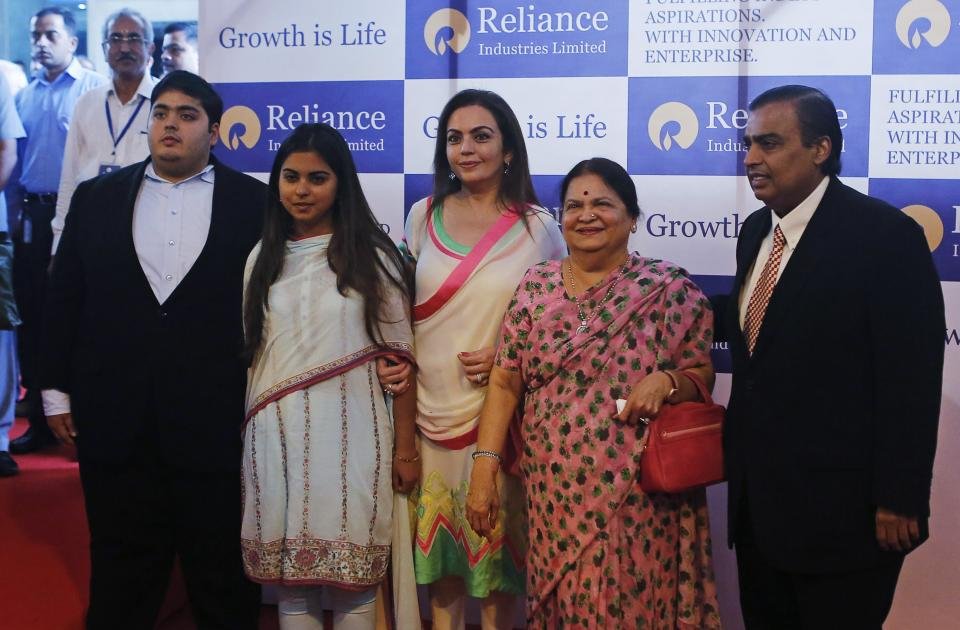 Mukesh Ambani (R), chairman of Reliance Industries Limited, poses with his son Akash, daughter Isha (2nd L), wife Nita (C) and mother Kokilaben, before addressing the annual shareholders meeting in Mumbai June 6, 2013. India's Reliance Industries Ltd plans to invest 1.5 trillion rupees ($26.4 billion) in its businesses over three years, Ambani told shareholders on Thursday. REUTERS/Danish Siddiqui (INDIA - Tags: BUSINESS)