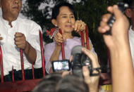 FILE - In this Nov, 13, 2010, file photo, then Myanmar's pro-democracy leader Aung San Suu Kyi talks to the supporters as she stands at the gate of her home in Yangon, Myanmar. Myanmar's military has taken control of the country under a one-year state of emergency and reports say State Counsellor Aung San Suu Kyi and other government leaders have been detained. (AP Photo/Khin Maung Win)