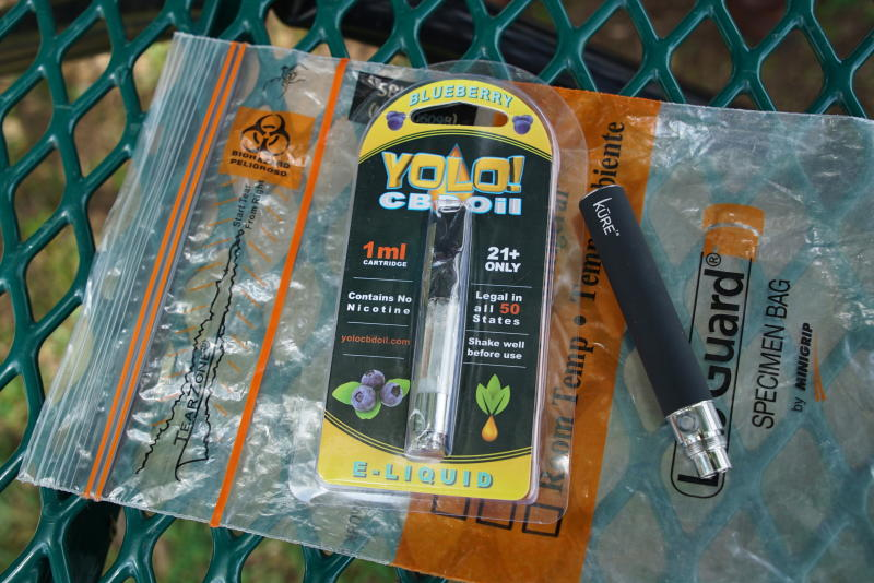 "FILE - In this May 8, 2019, file photo, a Yolo! brand CBD oil vape cartridge sits alongside a vape pen on a biohazard bag on a table at a park in Ninety Six, S.C. More than 50 people around Salt Lake City had been poisoned by the time the outbreak ended early last year, most by a vape called Yolo!, the acronym for ""you only live once."" (AP Photo/Allen G. Breed, File)"