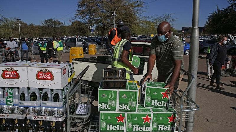People loading boxes of alcohol into cars