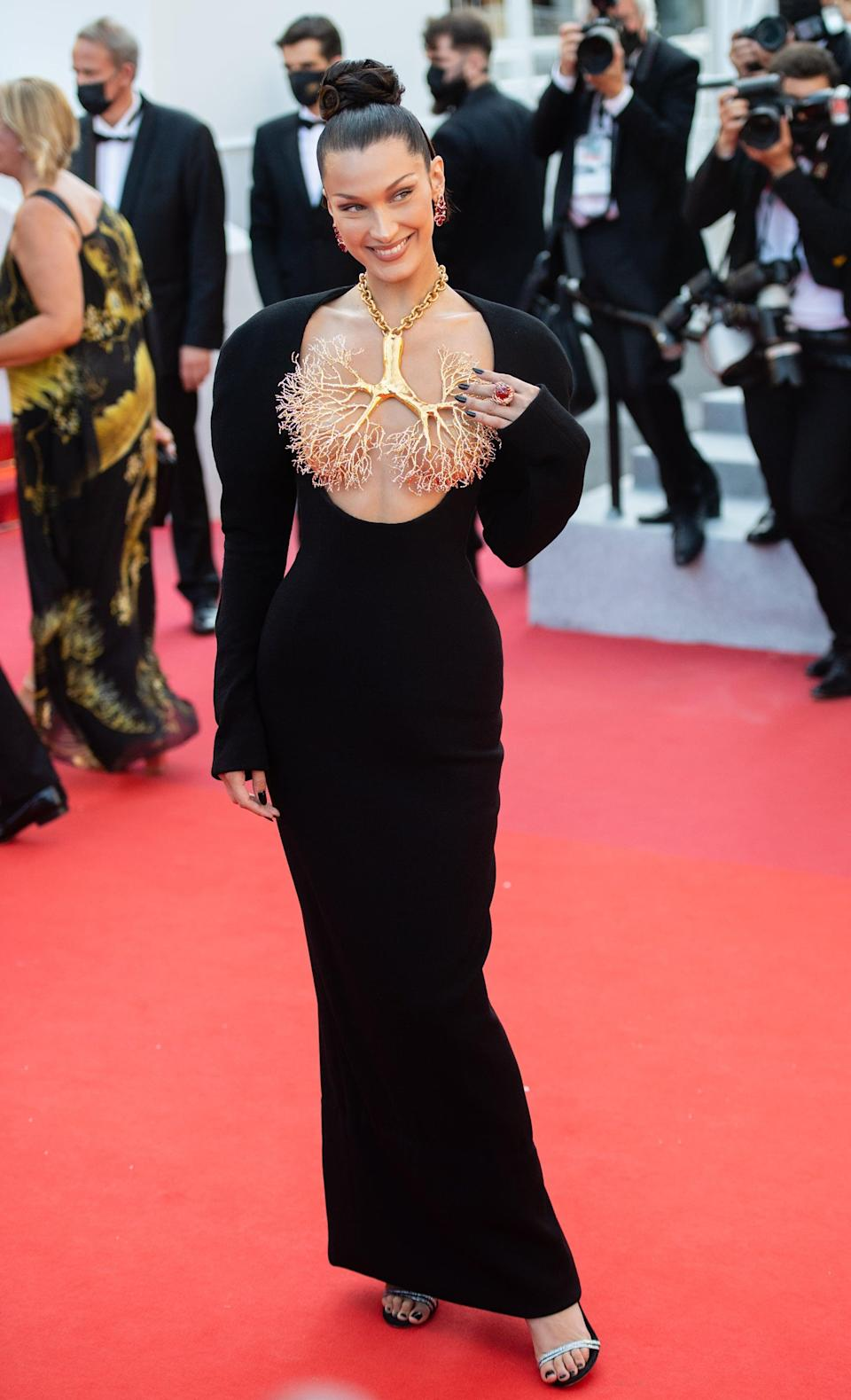 """<p>Wearing a <a href=""""https://www.popsugar.com/fashion/bella-hadid-schiaparelli-outfit-cannes-48413797"""" class=""""link rapid-noclick-resp"""" rel=""""nofollow noopener"""" target=""""_blank"""" data-ylk=""""slk:Schiaparelli dress"""">Schiaparelli dress</a> with a massive brass necklace in the shape of branched lungs adorned with rhinestones to cover her chest.</p>"""