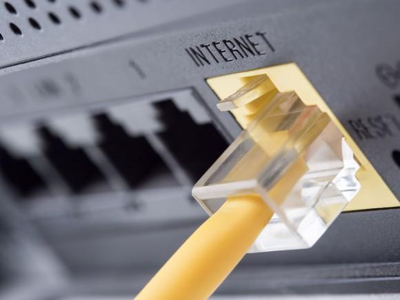 A yellow ethernet cable connected into the back of an internet modem.