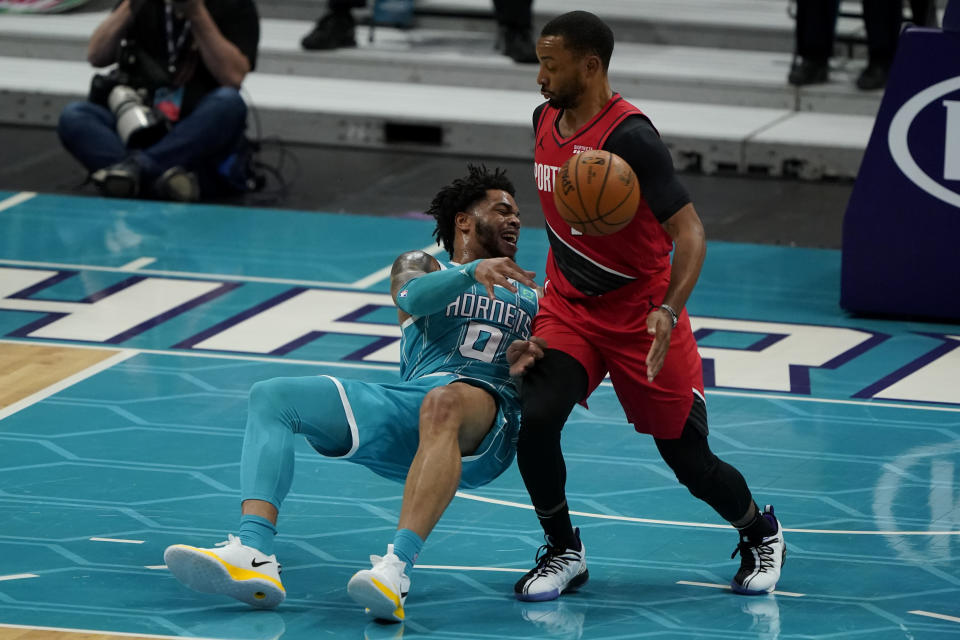 Charlotte Hornets forward Miles Bridges passes around Portland Trail Blazers forward Norman Powell during the first half in an NBA basketball game on Sunday, April 18, 2021, in Charlotte, N.C. (AP Photo/Chris Carlson)