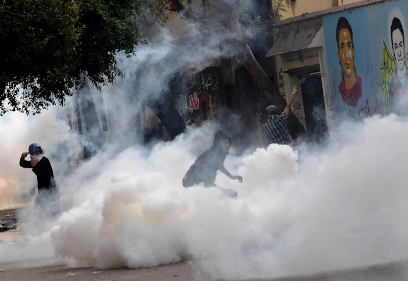 Egyptian protesters throw back tear gas canisters during clashes with security forces, near Tahrir Square in Cairo, Egypt, Wednesday, Nov. 21, 2012. Youth and security forces have been clashing in the area since Monday, with protesters hurling stones and firebombs and security forces firing birdshot and tear gas into the crowd. (AP Photo/Mohammed Asad)