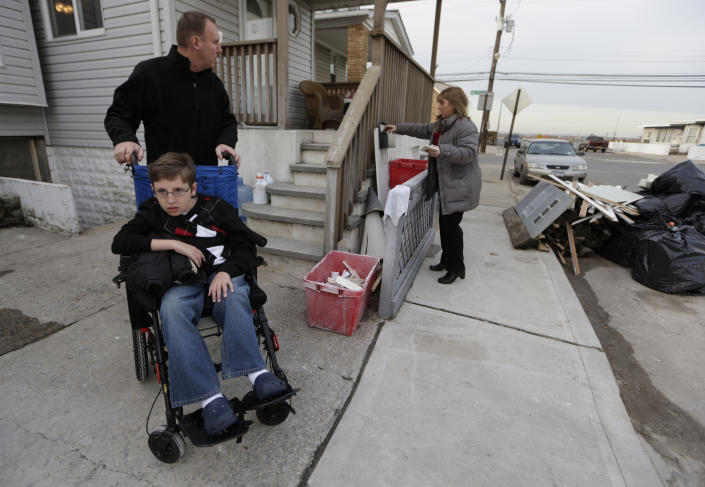 Chris Troy and his wheelchair-bound son Connor, 12, who suffers from a life-threatening neuromuscular disease, waits for wife Kerry Ann to get the mail in Long Beach, N.Y., Wednesday, Dec. 12, 2012, after visiting their home, which is under renovation after it was seriously damaged by Superstorm Sandy. Due to the kindness of strangers, the Troy's are staying in a nearby house in Point Lookout, N.Y. All the renovations to the home are being paid for by businessman Donald Denihan, who has ordered his workers to have the Long Beach house ready by Christmas. (AP Photo/Kathy Willens)