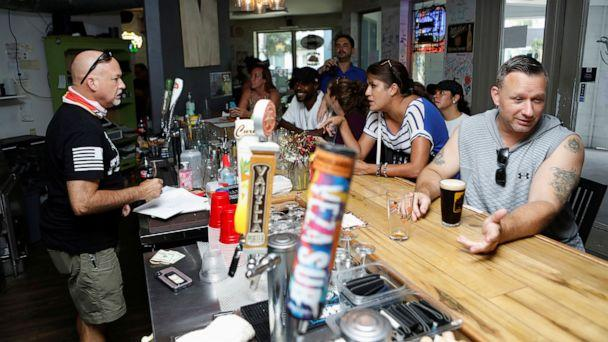 PHOTO: Bar patrons attend the reopen Florida 'maskless' rally and dinner held at 33 & Melt restaurant to protest mandatory face mask restrictions during the coronavirus pandemic in Windermere, Fla., July 11, 2020. (Octavio Jones/Reuters)