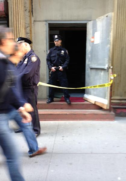 Crime scene tape and a New York City police officer block the service entrance to the site of a proposed Islamic community center in New York City, after a 5-foot-tall piece of landing gear has been discovered wedged between it and a luxury high-rise apartment building, Friday, April 26, 2013. The wreckage is believed to be from one of the hijacked planes destroyed in the Sept. 11, 2001 terrorist attacks on the World Trade Center. (AP Photo/Tom Hays)
