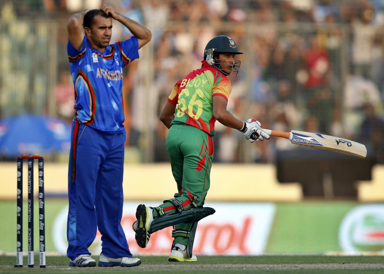 Afghanistan's bowler Karim Sadiq, left, reacts after Bangladesh's batsman Anamul Haque, right, hit a shot on his delivery during their ICC Twenty20 Cricket World Cup opening match in Dhaka, Bangladesh, Sunday, March 16, 2014. (AP Photo/Aijaz Rahi)