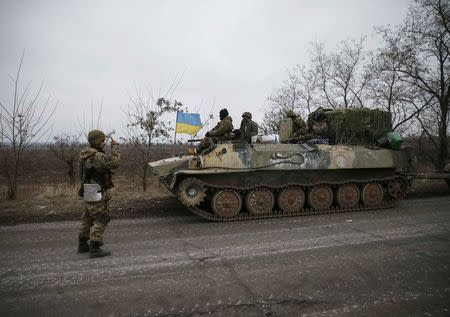 A convoy of Ukrainian armed forces including armoured personnel carriers, military vehicles and cannons prepare to move as they pull back from Debaltseve region, in Paraskoviyvka