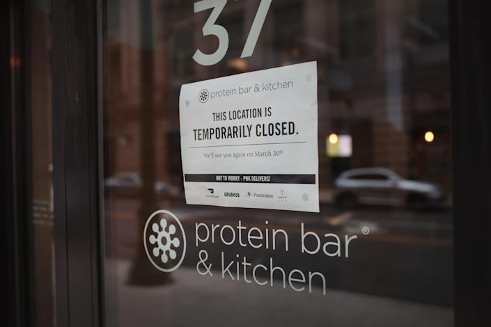 A sign hangs on the door of a shuttered restaurant in the Chicago Loop on March 19, 2020 in Chicago, Illinois. Restaurants, bars, and many other businesses are closed in the Loop and many office buildings are virtually deserted as companies have ordered their employees to work from home to avoid the spread of COVID-19.