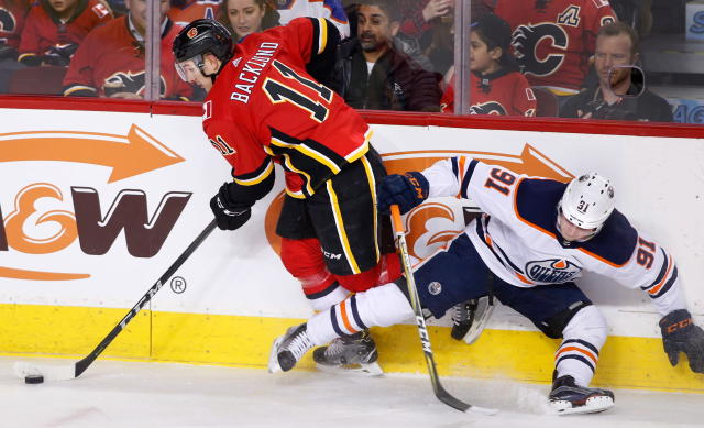 Edmonton Oilers' Drake Caggiula (31) is knocked off the puck by Calgary Flames' Mikael Backlund, of Sweden, during first period NHL hockey action in Calgary, Alberta, Saturday, March 31, 2018. (Larry MacDougal/The Canadian Press via AP)