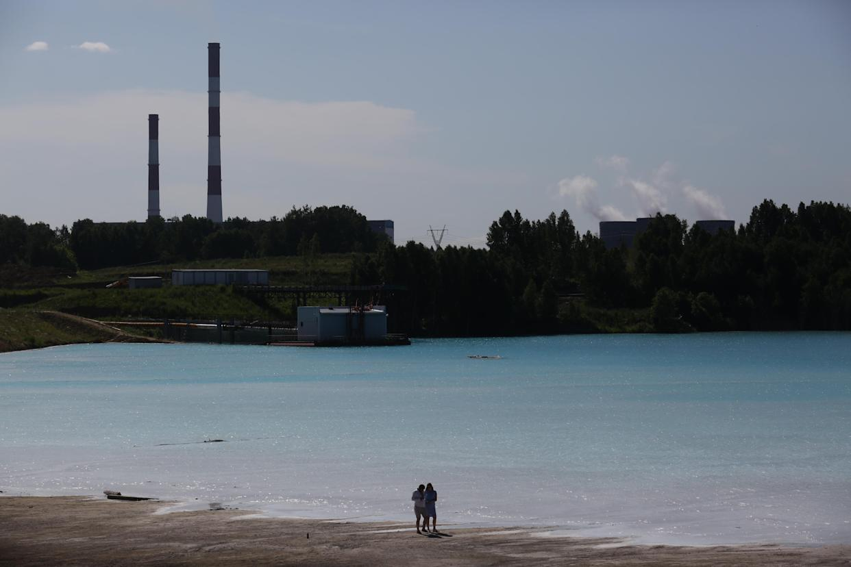 """A couple walks by a Novosibirsk energy plant's ash dump site - nicknamed the local """"Maldives"""" - on July 11, 2019. (Photo: Rostislav Netisov/AFP/Getty Images)"""