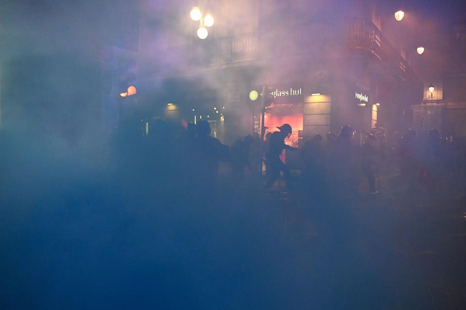 Members of the Catalan regional police force Mossos d'Esquadra stand amid a fog of lit flares after clashes erupted with protesters during a demonstration against new coronavirus restrictions in Barcelona on October 30, 2020. - One by one, Spain's regions have announced regional border closures in the hope of avoiding a new lockdown like in France. The central government unveiled a state of emergency to give regional authorities the tools to impose curfews and close their borders to anyone moving without just cause. (Photo by Josep LAGO / AFP) (Photo by JOSEP LAGO/AFP via Getty Images)