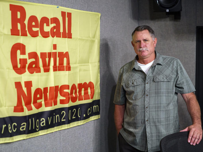 FILE — In this March 27, 2021, file photo Orrin Heatlie, the main organizer for the Recall of California Gov. Newsom campaign, poses with a banner before recording a radio program at KABC radio station studio in Culver City, Calif. Newsom is facing the second recall of a governor in California history, and the last day to vote is Sept. 14, 2021. The coronavirus has been a dominating factor in the recall, which was first launched last year. (AP Photo/Damian Dovarganes, File)