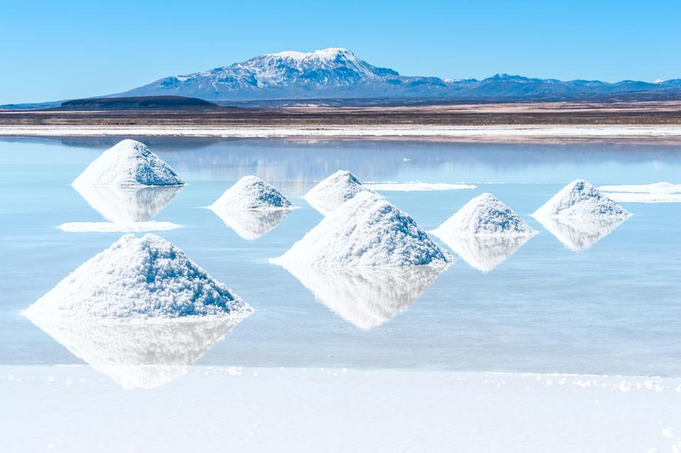 Lithium brine pool, with mounds of lithium salts in foreground, and mountains and blue sky in background.