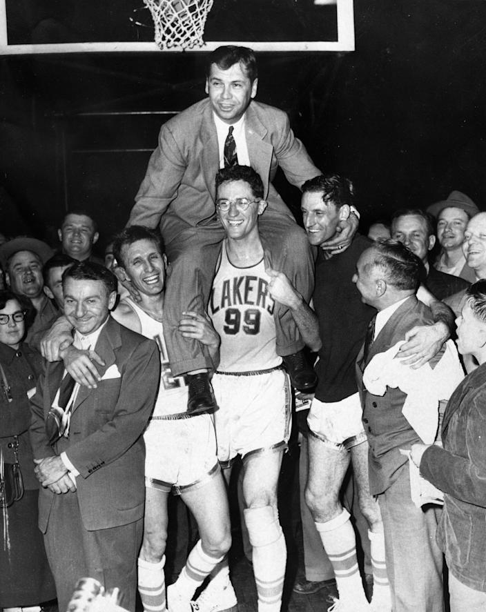 Minneapolis Lakers hoist coach John Kundla and carry him to their dressing room.