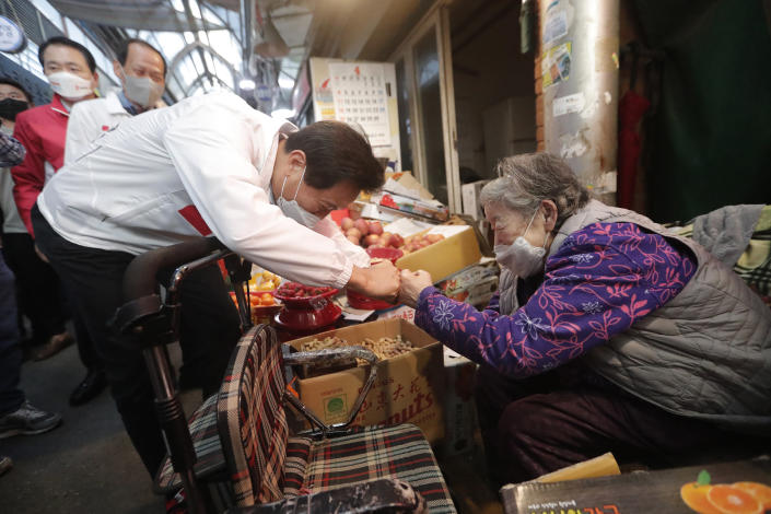 Oh Se-hoon, left, the candidate of the main opposition People Power Party, bumps fists with a vendor during a campaign for the April 7 Seoul mayoral by-election at a market in Seoul, South Korea, Tuesday, April 6, 2021. (AP Photo/Ahn Young-joon)