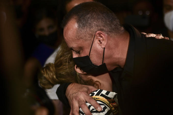 Keila Ortiz, the mother of Keishla Rodriguez, hugs Police Commissioner Antonio Lopez after boxer Felix Verdejo was arrested in connection with the death of her 27-year-old pregnant daughter whose body was found in a lagoon in San Juan, Puerto Rico, Sunday, May 2, 2021. (AP Photo/Carlos Giusti)