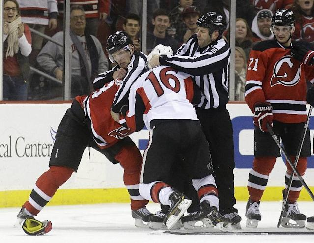 Officials intervene as Ottawa Senators left wing Clarke MacArthur (16) and New Jersey Devils defenseman Anton Volchenkov, left, of Russia, flight at the end of the second period of an NHL hockey game, Wednesday, Dec. 18, 2013, in Newark, N.J. (AP Photo/Julio Cortez)