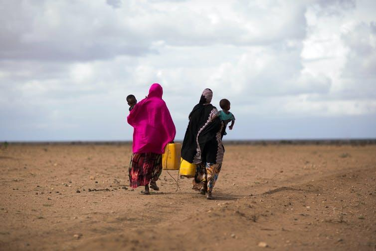 Two women and their babies walk across a dry desert.