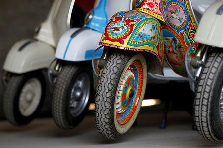 A restored Vespa scooter painted in Pakistani truck art style, is parked alongside traditionally-coloured scooters at a Vespa restoration and repair workshop in Islamabad, Pakistan February 27, 2018. REUTERS/Caren Firouz