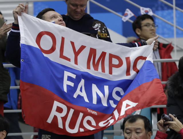 A fan holds up a flag as he cheers during the preliminary round of the men's hockey game between the team from Russia and Slovenia at the 2018 Winter Olympics in Gangneung, South Korea, Friday, Feb. 16, 2018. (AP Photo/Julio Cortez)