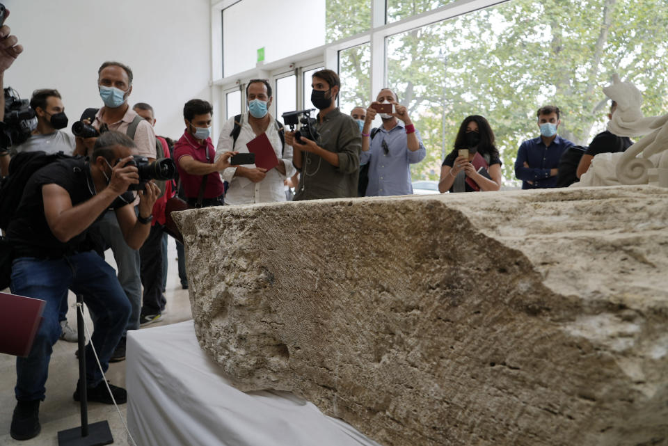 Photographers take pictures during the presentation to the press of an archeological finding emerged during the excavations at a Mausoleum in Rome, Friday, July 16, 2021. The monumental pomerial stone is dating back to Roman Emperor Claudio and was used to mark the 'pomerium' the sacred boundaries of the 'Urbe', the city of Rome, during the Roman empire. (AP Photo/Domenico Stinellis)